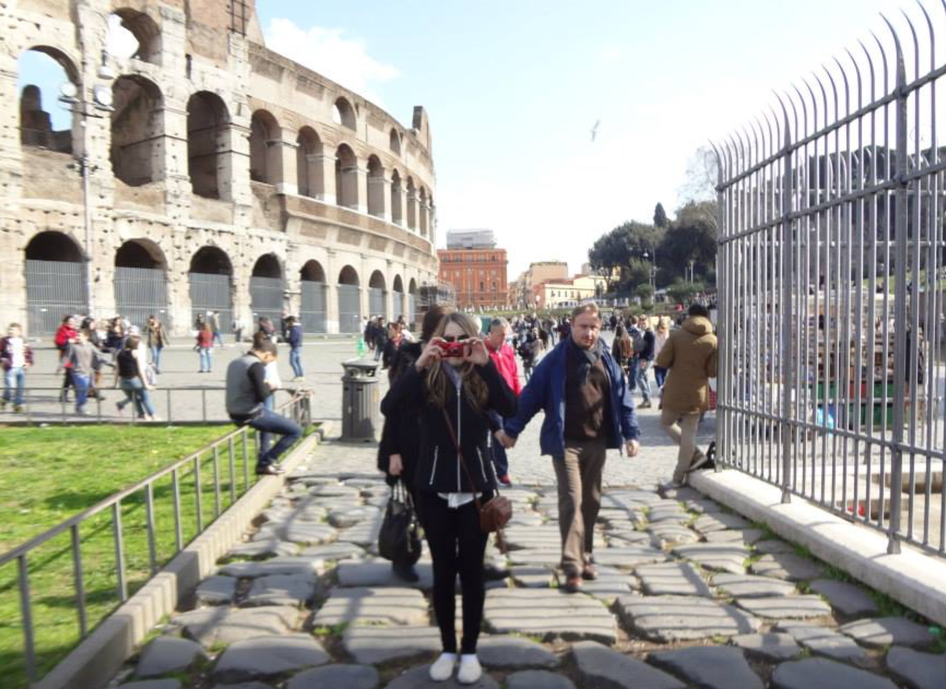 a woman stands on a cobbled street in front of the colloseum taking a photo of the person who is photographing her