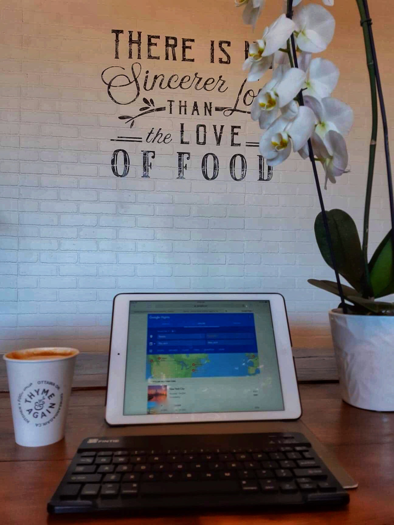 a tablet sits open to google flights with the backdrop of a coffee shop