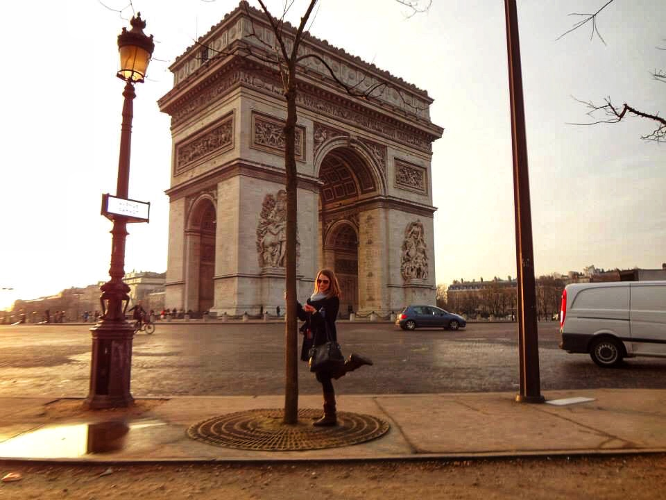 A picture of a girl posing in front of the arc de triomph