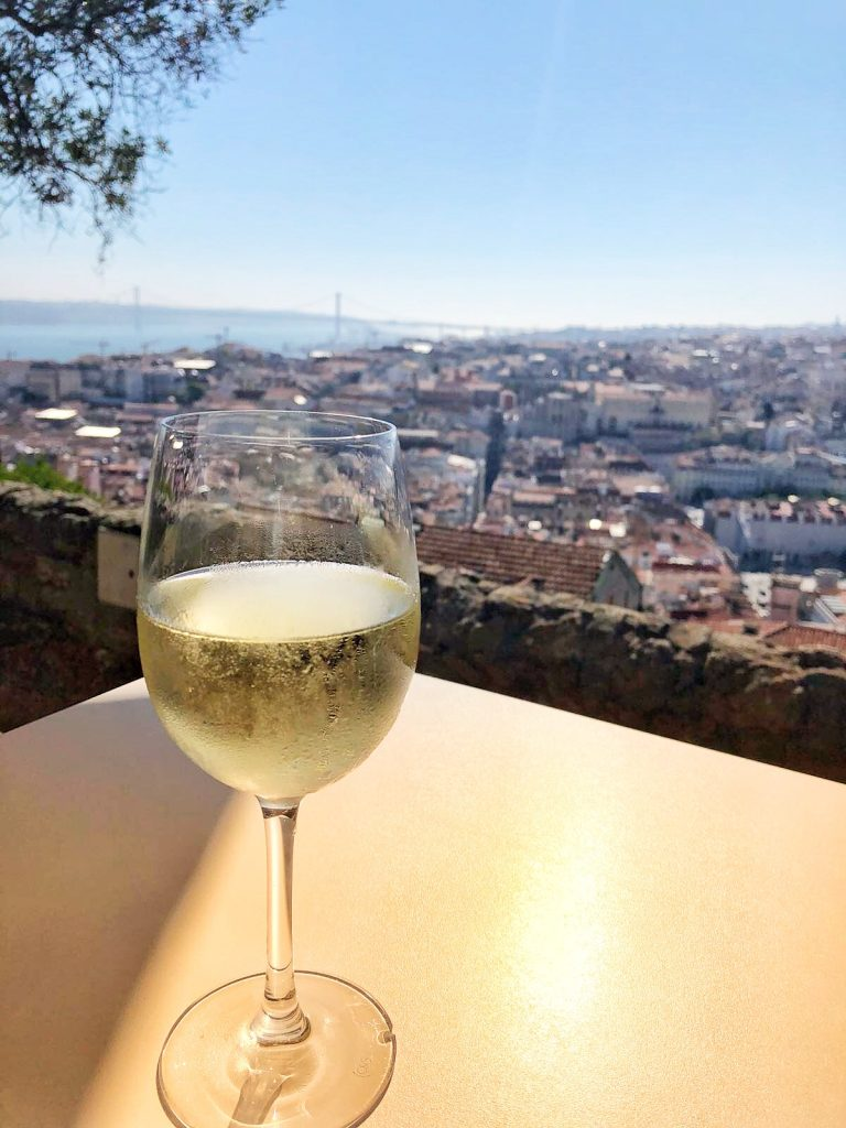 a glass of white wine is perched on a table with a dramatic view of Lisbon clay roofs in the city below