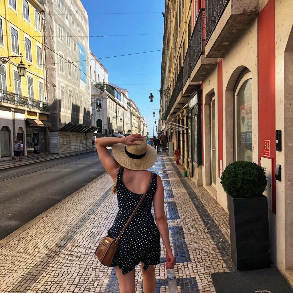 A girl walking down a picturesque street in Lisbon shows why Portugal should be on your 2019 bucket list by coffee and a view