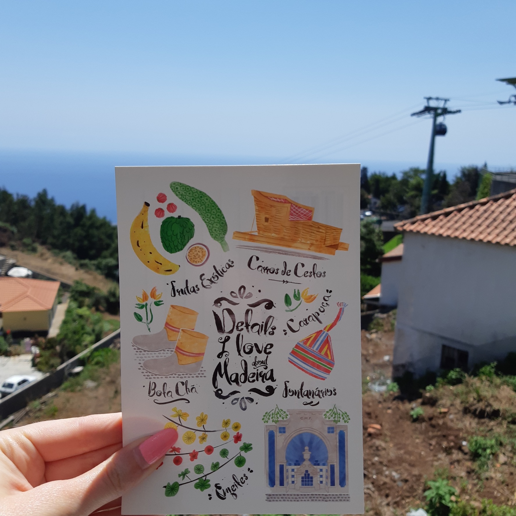 a girl holds up a postcard displayng unique things about madeira with the background of funchal below and the ocean behind