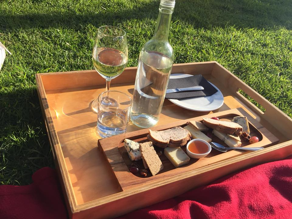 a picnic on a wooden tray with wine, cheese and breads