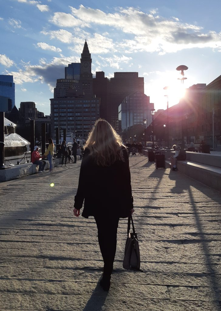 a woman walks towards the setting sun along the Boston Harbour