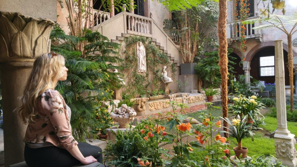 a woman sits perched on a ledge looking at a garden inside the Isabella Gardner Museum