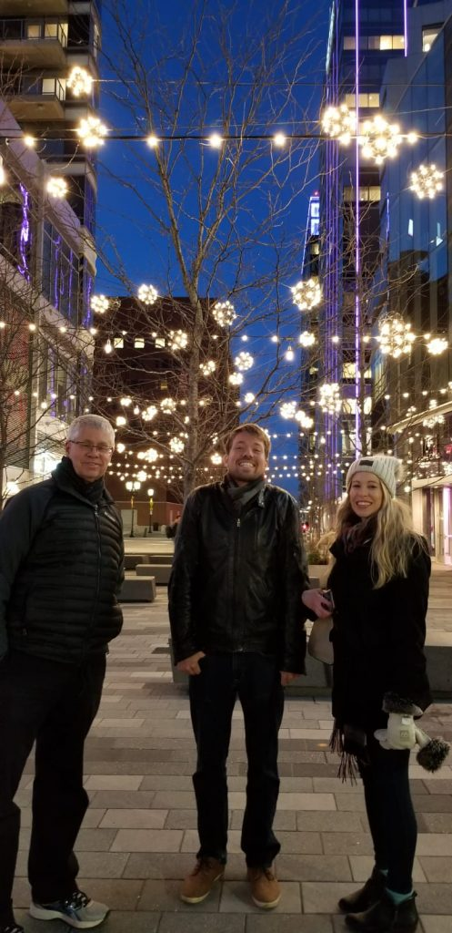 two men and a woman stand beneathe twinkle lights in the One Seaport shopping district in Boston