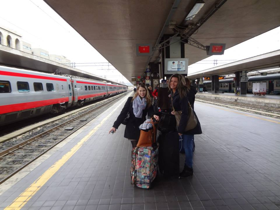 two women wait with their baggage at a European train station